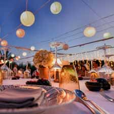 Photo of setup for outdoor party showing hanging lights, centerpieces and table settings