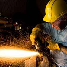 photo of welder in hard hat with sparks flying