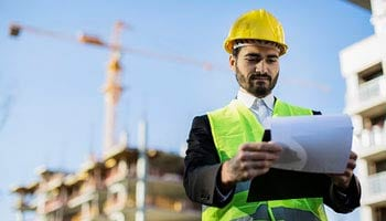 photo of a construction project manager in front of a construction site looking over papers